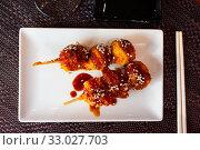 Купить «Chicken balls in spicy sauce with sesame seeds on a skewer. Japanese cuisine», фото № 33027703, снято 26 февраля 2020 г. (c) Яков Филимонов / Фотобанк Лори