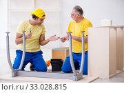 Two contractors carpenters working indoors. Стоковое фото, фотограф Elnur / Фотобанк Лори