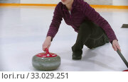 Купить «Curling training - a young woman pushes off from the stand with a stone biter», видеоролик № 33029251, снято 5 июня 2020 г. (c) Константин Шишкин / Фотобанк Лори