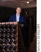 Wine producer controlling wine aging in winery vault. Стоковое фото, фотограф Яков Филимонов / Фотобанк Лори