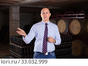 Сonfident winemaker inviting to wine cellar, demonstrating bottles with aging wine on racks. Стоковое фото, фотограф Яков Филимонов / Фотобанк Лори