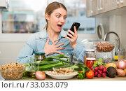 Купить «Portrait of glad woman looking at mobile phone while making dish on kitchen at home», фото № 33033079, снято 6 августа 2020 г. (c) Яков Филимонов / Фотобанк Лори