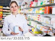 Купить «Woman pharmacist standing in drugstore», фото № 33033115, снято 28 февраля 2018 г. (c) Яков Филимонов / Фотобанк Лори