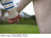 Купить «Young couple holding hands in the garden», фото № 33033723, снято 28 ноября 2019 г. (c) Wavebreak Media / Фотобанк Лори