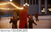 Купить «A family of mother and two kids skating on public ice rink at evening in bright lights», видеоролик № 33034203, снято 11 июля 2020 г. (c) Константин Шишкин / Фотобанк Лори