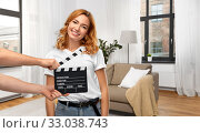 Купить «happy woman at studio and hands with clapperboard», фото № 33038743, снято 6 октября 2019 г. (c) Syda Productions / Фотобанк Лори
