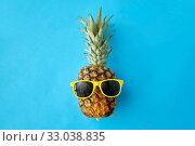 pineapple in yellow sunglasses on blue background. Стоковое фото, фотограф Syda Productions / Фотобанк Лори