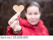 Купить «Woman showing heart shape in stretched hand, red jacket, blurred head», фото № 33039091, снято 6 января 2020 г. (c) Кекяляйнен Андрей / Фотобанк Лори