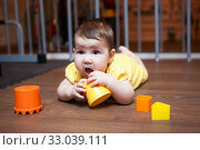 Baby girl 7 months old chewing on teething toy, while lying on hardwood floor. Стоковое фото, фотограф Кекяляйнен Андрей / Фотобанк Лори