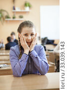 Primary school pupil sitting at the desk in classroom, preteen smiling girl portrait. Стоковое фото, фотограф Кекяляйнен Андрей / Фотобанк Лори