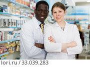 Купить «Experienced male and female pharmacists standing in interior», фото № 33039283, снято 2 марта 2018 г. (c) Яков Филимонов / Фотобанк Лори