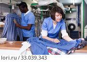 Female laundry worker examining clean garments. Стоковое фото, фотограф Яков Филимонов / Фотобанк Лори