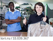 Купить «Satisfied female client with clean garment», фото № 33039367, снято 15 января 2019 г. (c) Яков Филимонов / Фотобанк Лори