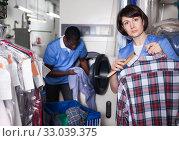 Купить «Female laundry worker during daily work», фото № 33039375, снято 15 января 2019 г. (c) Яков Филимонов / Фотобанк Лори