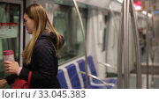 Купить «Positive young woman absorbed in her smartphone while traveling in subway car», видеоролик № 33045383, снято 17 января 2020 г. (c) Яков Филимонов / Фотобанк Лори