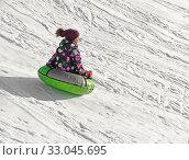 Зимние забавы. Девочка спускает с горы на ватрушке (2020 год). Редакционное фото, фотограф Валерия Попова / Фотобанк Лори