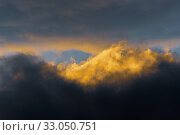Fluffy clouds illuminated by disappearing rays at sunset and dark thunderclouds floating across sunny blue sky to change season weather. Стоковое фото, фотограф А. А. Пирагис / Фотобанк Лори