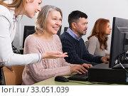 Female teacher helping smiling mature woman. Стоковое фото, фотограф Яков Филимонов / Фотобанк Лори