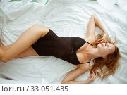 Купить «Beautiful sexy slim girl with a perfect figure lies on a white sheet in black bodysuit», фото № 33051435, снято 9 сентября 2017 г. (c) katalinks / Фотобанк Лори