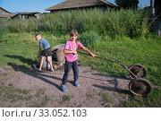 Купить «Мальчик набирает воду в флягу, девочка стоит с тележкой у сельской колонки в летний солнечный день», фото № 33052103, снято 2 августа 2019 г. (c) Светлана Попова / Фотобанк Лори