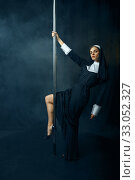 Купить «Sexy nun in cassock dances on pole like a stripper», фото № 33052327, снято 14 ноября 2019 г. (c) Tryapitsyn Sergiy / Фотобанк Лори