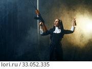 Купить «Young nun in a cassock holds assault rifle», фото № 33052335, снято 14 ноября 2019 г. (c) Tryapitsyn Sergiy / Фотобанк Лори