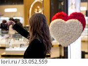 Купить «Красивая девушка делает селфи в торговом центре Метрополис на фоне витрины ювелирного магазина с оформлением приуроченным к Дню Святого Валентина в городе Москве, Россия», фото № 33052559, снято 8 февраля 2020 г. (c) Николай Винокуров / Фотобанк Лори