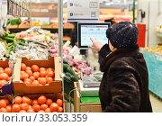 Женщина взвешивает продукты в  магазине (2017 год). Редакционное фото, фотограф Юрий Морозов / Фотобанк Лори