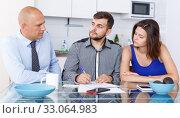 Купить «Unhappy young couple signing financial agreement with social worker», фото № 33064983, снято 6 июля 2018 г. (c) Яков Филимонов / Фотобанк Лори