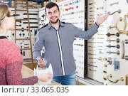 Купить «happy male seller assisting woman in choosing door handles in shop», фото № 33065035, снято 5 апреля 2017 г. (c) Яков Филимонов / Фотобанк Лори