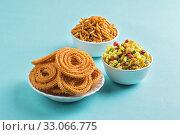 Indian Snack : Chakli, chakali or Murukku and Besan (Gram flour) Sev and chivada or chiwada on blue background. Diwali Food. Стоковое фото, фотограф Dipak Chhagan Shelare / easy Fotostock / Фотобанк Лори