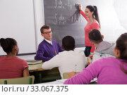 Купить «cute student girl solves task near blackboard», фото № 33067375, снято 21 февраля 2020 г. (c) Татьяна Яцевич / Фотобанк Лори