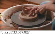 Купить «Pottery - master with finger is making the bottom for a clay bowl on the potter's wheel», видеоролик № 33067827, снято 6 апреля 2020 г. (c) Константин Шишкин / Фотобанк Лори