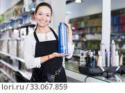 Smiling girl hairstylist in apron demonstration shampoo in studio. Стоковое фото, фотограф Яков Филимонов / Фотобанк Лори