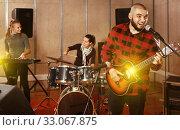 Купить «Bearded guy soloist playing guitar in studio», фото № 33067875, снято 26 октября 2018 г. (c) Яков Филимонов / Фотобанк Лори