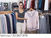 Купить «Shop assistant demonstrating jacket on hanger», фото № 33067919, снято 10 октября 2018 г. (c) Яков Филимонов / Фотобанк Лори