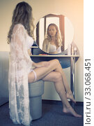 Купить «Beautiful young woman in white lace peignoir sits in front of a mirror in a boudoir in bedroom», фото № 33068451, снято 20 июля 2016 г. (c) katalinks / Фотобанк Лори