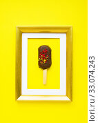 Brownie cake in form of popsicle in golden frame on yellow background. Dessert as Art. Стоковое фото, фотограф Papoyan Irina / Фотобанк Лори