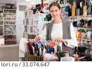 Купить «Female seller showing ribbons», фото № 33074647, снято 18 октября 2019 г. (c) Яков Филимонов / Фотобанк Лори