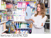 Купить «Attractive woman holding bottle of rinse aid», фото № 33074723, снято 19 октября 2019 г. (c) Яков Филимонов / Фотобанк Лори