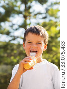 Купить «Child boy 5 years old in white t-shirt with ice cream in  summer outdoors. Kid licks tongue ice cream in waffle cup», фото № 33075483, снято 16 июля 2019 г. (c) Юлия Бабкина / Фотобанк Лори