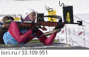 Sportswoman biathlete aiming, rifle shooting in prone position. Biathlete Andreeva Victoriya in shooting range. Junior biathlon competitions East of Cup (2019 год). Редакционное видео, видеограф А. А. Пирагис / Фотобанк Лори
