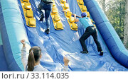 Купить «Group of excited people passing obstacles on inflatable arena at amusement park», видеоролик № 33114035, снято 4 июля 2020 г. (c) Яков Филимонов / Фотобанк Лори