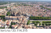 Купить «Scenic panoramic aerial view of residential areas of Narbonne with medieval Roman Catholic Cathedral on sunny summer day, France», видеоролик № 33114315, снято 30 августа 2019 г. (c) Яков Филимонов / Фотобанк Лори