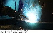Купить «Working welder at the factory in a protective suit welds metal details in shop. Industrial theme», видеоролик № 33123751, снято 16 февраля 2020 г. (c) Алексей Кузнецов / Фотобанк Лори