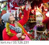Купить «Positive smiling woman at fair near counter with Christmas gifts», фото № 33126231, снято 1 декабря 2018 г. (c) Яков Филимонов / Фотобанк Лори