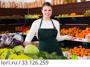 Купить «Portrait of young female in apron selling fruits and vegetables», фото № 33126259, снято 31 января 2019 г. (c) Яков Филимонов / Фотобанк Лори
