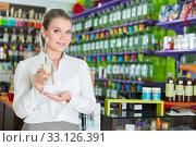 Купить «Female seller showing perfume», фото № 33126391, снято 24 апреля 2018 г. (c) Яков Филимонов / Фотобанк Лори