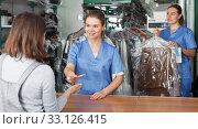 Купить «Worker returning clothing after dry cleaning», фото № 33126415, снято 9 мая 2018 г. (c) Яков Филимонов / Фотобанк Лори