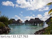Купить «Wooden walkways over the water of the blue tropical sea to authentic traditional Polynesian thatched roof houses», фото № 33127763, снято 18 июня 2011 г. (c) Куликов Константин / Фотобанк Лори